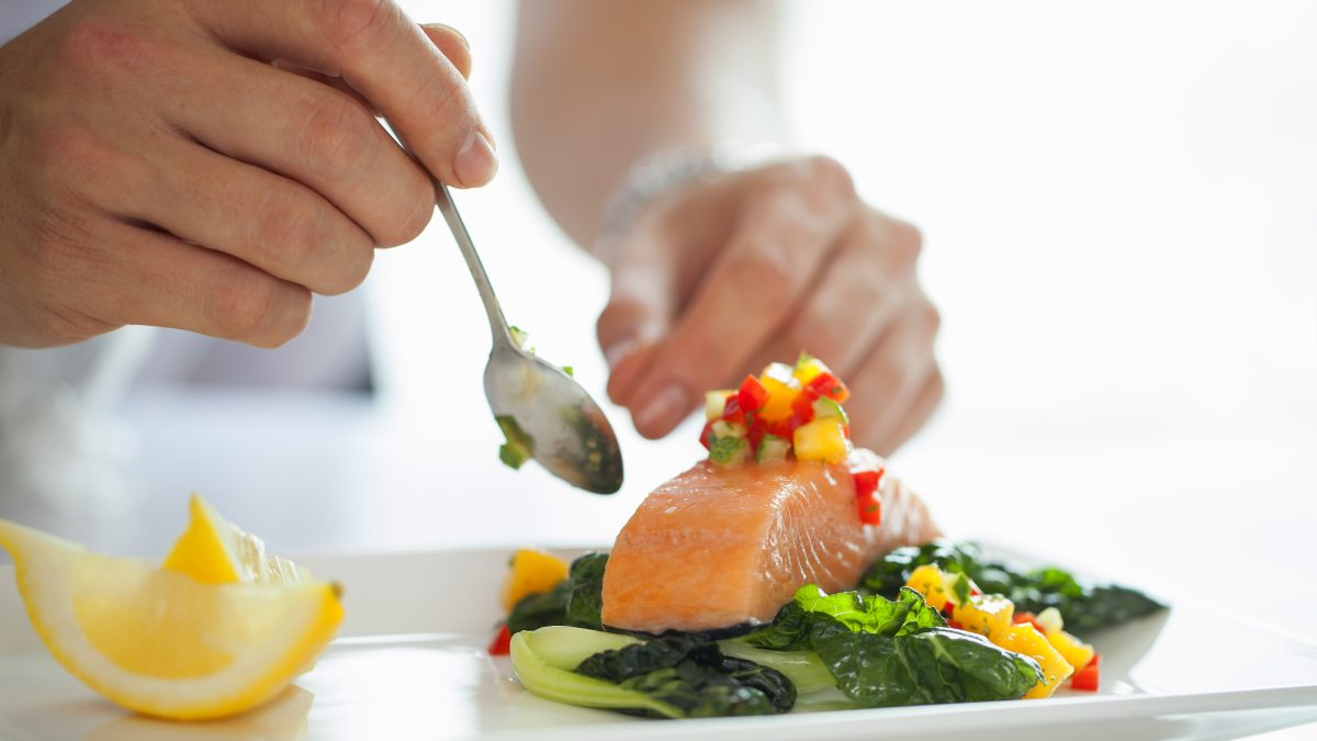 A chef diligently prepares a salmon filet.